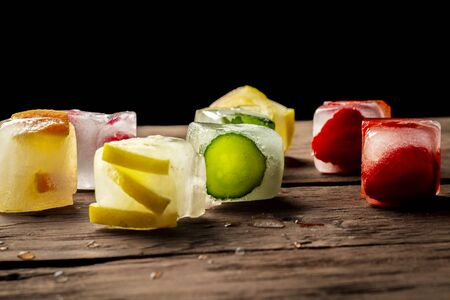Ice cubes with fruit on wooden background. Hot summer concept, dessert. 写真素材