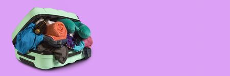 Plastic suitcase with wheels, overflowing things on a pink background. Travel concept, vacation trip, visit to relatives. Banner.