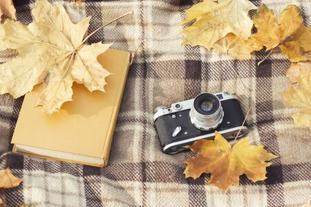 Retro camera and book lay on a brown checkered plaid with yellow autumn leaves. Concept of the fall and outdoor recreation. Flat lay, top view.