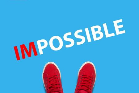 Legs in red sneakers on a blue background and text Impossible. Concept impossible tasks before man. Flat lay, top view. 写真素材