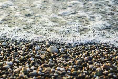 Beach with pebbles and surf at dusk or dawn.