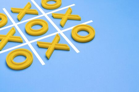 Yellow plastic crosses and a toe and a ruled field for playing tic-tac-toe on a blue background. Concept XO Win Challenge. Educational game for kids. 写真素材