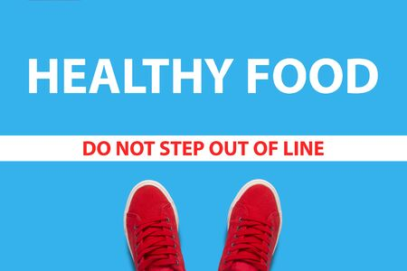 Legs in red sneakers on a blue background with a restrictive white line with text do not step out of line and a healthy food behind the line. Concept is difficult with a healthy food to harmful food.
