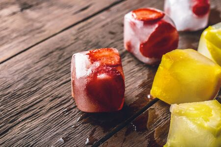 Ice cubes with fruit on wooden background. Hot summer concept, dessert. Reklamní fotografie