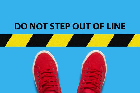 Legs in red sneakers on a blue background with a restrictive yellow black stripe with text Do not step out of line. Concept Limitations of Action. Flat lay, top view.