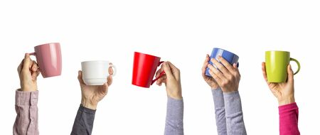 Many different hands holding multi colored cups of coffee on a white background. Female and male hands. Concept of a friendly team, a coffee break, meeting friends, morning in the team. Banner.