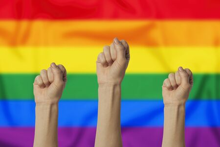 Female hand clenched into a fist and raised up on a background with LGBT flag. Concept of power, rebellion, unity, revolution.