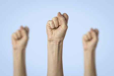 Female hands clenched into a fist and raised up on a blue background. Concept of power, rebellion, unity, revolution, riot.