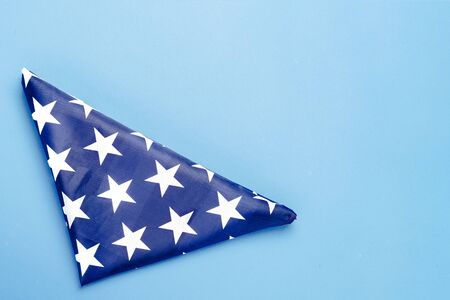 Folded USA flag on a blue background. Concept Memorial Day, Independence Day, July 4th. Flat lay, top view.
