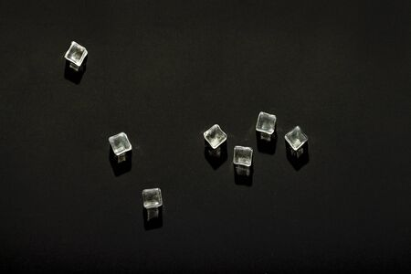 Ice cubes on a black background. The concept of heat, cooling. Natural light. Flat lay, top view. 스톡 콘텐츠