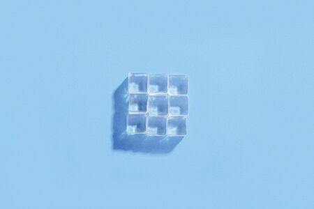 Ice cubes on a blue background. The concept of heat, cooling. Natural light. The shape of the square. Flat lay, top view.
