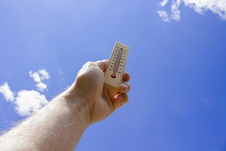 The male hand holds a thermometer against the blue sky. The concept of heat, global warming.