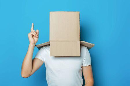 Hombre joven con una camiseta blanca con una caja de cartón en la cabeza hace un gesto con las manos sobre un fondo azul.