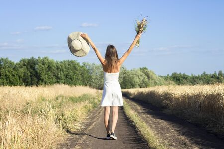 Young beautiful woman in a white dress and hat holds a bouquet with wildflowers on the road between the milky field. Concept of outdoor recreation, a trip to the village. Stock fotó