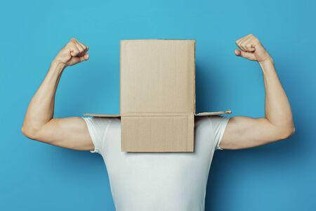 Hombre joven con una camiseta blanca con una caja de cartón en la cabeza sobre un fondo azul. Hace un gesto con la mano Fuerza y potencia, culturismo, deporte.
