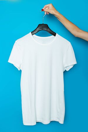 Female hand holds a white T-shirt without a picture on a trempel on a blue background. Archivio Fotografico - 129422928