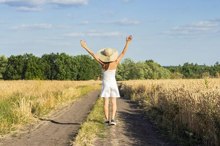 Beautiful young woman in a white dress and hat walks along the road between two fields with wheat. Concept of outdoor recreation, a trip to the village, vacation.
