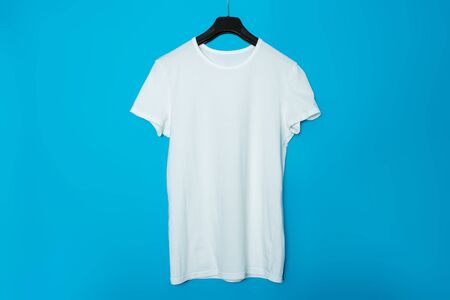 White T-shirt without a pattern on a trempel on a blue background. Mock up. Archivio Fotografico - 129423276