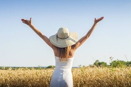 Young beautiful woman in a white dress and a hat raises her hands up on the field. Stock fotó