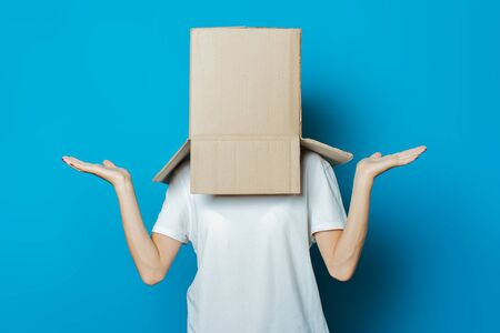 Young woman with a cardboard box on her head on a blue background. Banco de Imagens