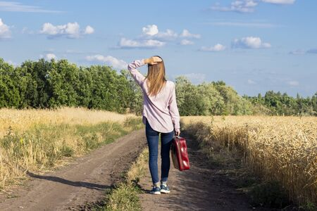 Beautiful young woman with a suitcase is walking along a road between wheat fields in the background. Travel concept, vacation.