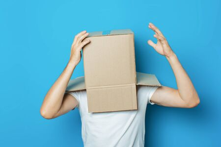 Young man in a white T-shirt with a cardboard box on his head makes a gesture with his hands on a blue background. Banco de Imagens - 129423488