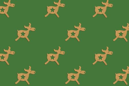 Wooden Christmas toy Deer is lined with a pattern on a green isolated background. Merry Christmas and Happy New Year concept. Minimalistic style. Flat lay, top view.