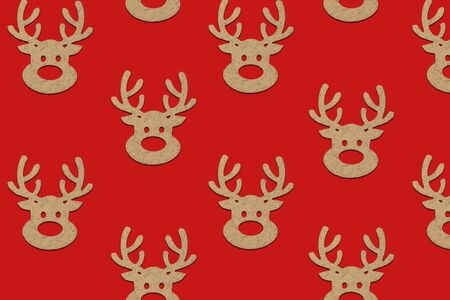 Wooden Christmas toys head of a deer is lined with a pattern on a red background. Merry Christmas and Happy New Year concept. Minimalistic style. Flat lay, top view.