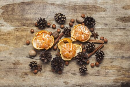 Tangerines, cones, spices on a wooden background. Concept of New Year and Christmas, Christmas drink Mulled wine. Flat lay, top view Stock fotó
