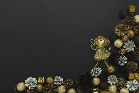 Pine cones and nuts painted in golden, black, white colors, Christmas-tree decorations on a black background. Concept of Happy New Year and Merry Christmas. Flat lay, top view.