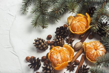 Tangerines without peel, Christmas tree branches, spices, cinnamon, cones on a white stone background. Concept of Christmas, New Year, Mulled Wine Stock fotó