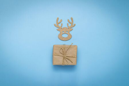 Gift box in craft paper and Wooden Christmas toy. Deer head on a blue background. Gift concept for a loved one, for a holiday, birthday, congratulations. Flat lay, top view.