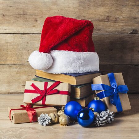 A stack of books, Santa Clauss cap, cones, Christmas-tree decorations, gift boxes on a wooden background. Concept of New Year and Merry Christmas Stock fotó
