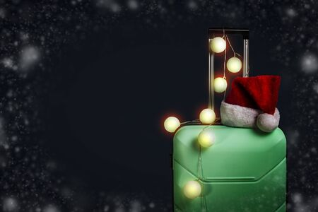 Plastic suitcase, Santa Claus cap and garland on a dark blue background with snow. Concept of travel, business trips, trips to visit friends and relatives on Christmas holidays. New Years journey. Stock fotó