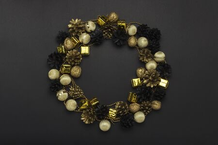 Pine cones and nuts painted in golden, black, white colors, Christmas-tree decorations on a black background. Circle shape. Concept of Happy New Year and Merry Christmas. Flat lay, top view.