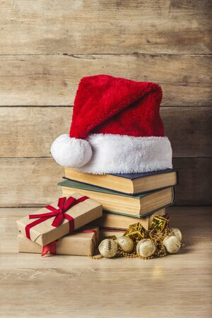 A stack of books, Santa Clauss hat Christmas-tree decorations gift boxes on a wooden background. Concept of New Year and Merry Christmas