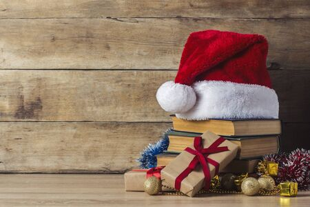 A stack of books, Santa Clauss hat, gift boxes on a wooden background. Concept of New Year and Merry Christmas