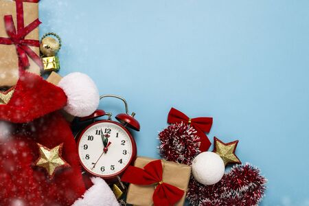 Red alarm clock, Santa Claus hat, Christmas-tree decorations, gifts on a blue background. Merry Christmas and happy new year concept. Flat lay, top view. Imagens