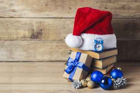 A stack of books, Santa Clauss cap, an alarm clock, cones, Christmas-tree decorations, gift boxes on a wooden background. Concept of New Year and Merry Christmas