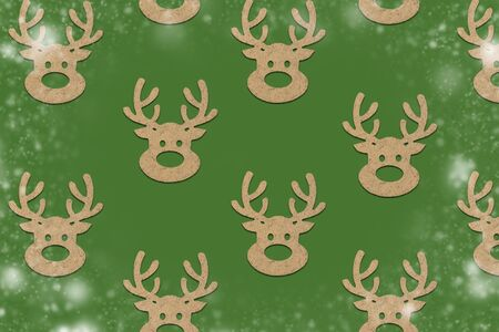 Wooden Christmas toys head of a deer is lined with a pattern on a green background with the effect of falling snow. Merry Christmas and Happy New Year concept. Minimalistic style. Flat lay, top view. Stock fotó