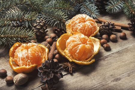 Tangerines, Christmas tree branches, cones, spices on a wooden background. Concept of New Year and Christmas, Christmas drink Mulled wine