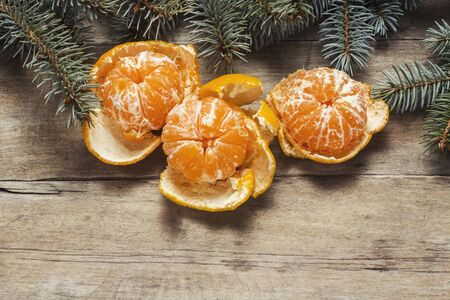 Tangerines and Christmas tree branches on a wooden background. Concept of New Year and Christmas. Flat lay, top view