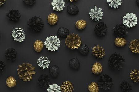 Pine cones and nuts painted in golden, black, white colors on a black background. Pattern. Concept of Happy New Year and Merry Christmas. Flat lay, top view.