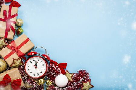 Red alarm clock, Christmas decorations, gifts on a blue background. Merry Christmas and happy new year concept. Copy Space. Flat lay, top view. Imagens