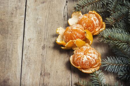 Tangerines and Christmas tree branches on a wooden background. Concept of New Year and Christmas Stock fotó