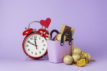 Small plastic bag for shopping, gift boxes, heart on a stick, red alarm clock, Christmas decorations, violet background. Concept of pre-holiday shopping, Christmas sale, Black Friday, Cyber Monday. Stock Photo