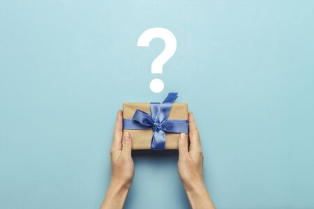 Female hands hold a gift box with a blue ribbon on a blue background with a question mark. Surprise concept, waiting for a gift for the holidays, birthday, christmas, wedding. Flat lay, top view. 写真素材
