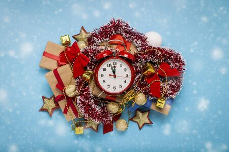 Red alarm clock, Christmas decorations, gifts on a blue background with snow. Merry Christmas and happy new year concept. Flat lay, top view.