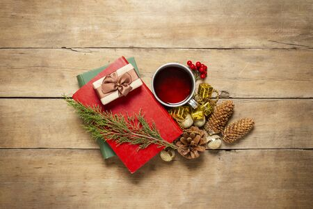 Books, a metal cup with tea and cones, a sprig of a Christmas tree, gift on a wooden background. Concept of the onset of autumn, winter, country house, winter holidays. Flat lay, top view. Stockfoto