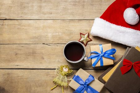 Cup with hot tea, Santa Claus hat, gift, Christmas decorations, books on a wooden background. The concept of Christmas, winter holidays, new year. Flat lay, top view.